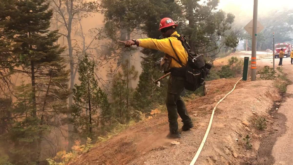 Un capitán de bomberos señala dónde los equipos deben llevar una manguera por una colina mie ...