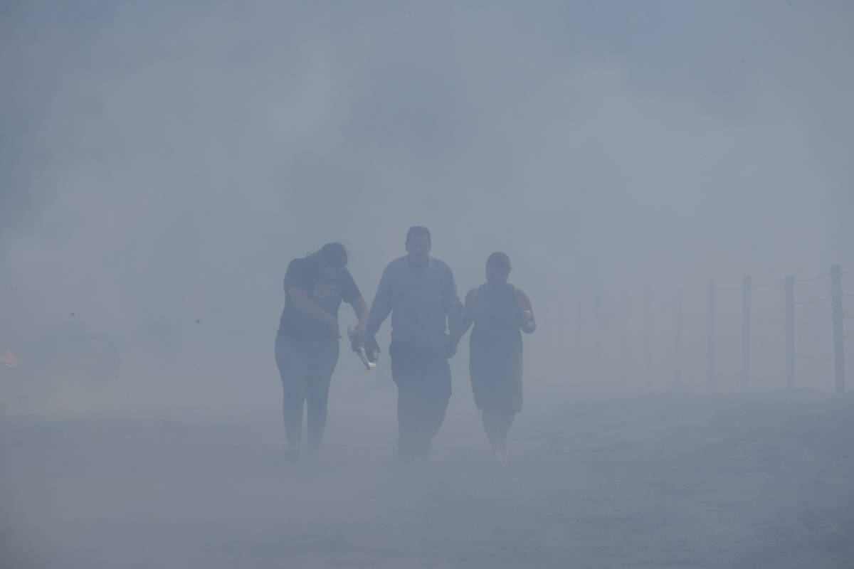 José Lamas y su hija Astrid Covarrubias caminan por el humo y por los restos carbonizados que ...