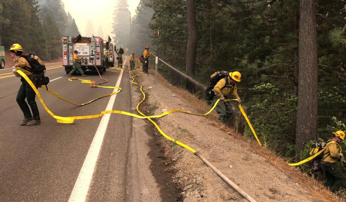 Equipos de bomberos llevan una manguera por una colina mientras el Caldor Fire arde a ambos lad ...