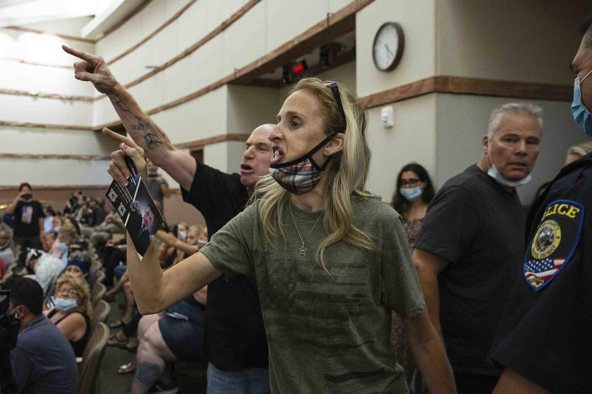 Manifestantes contra el mandato COVID-19 hacen un gesto mientras son escoltados fuera de la reu ...
