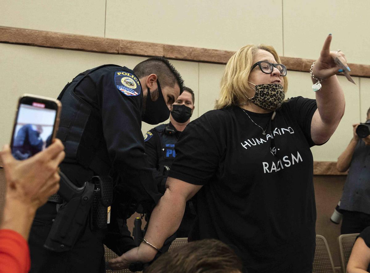 Una manifestante, que protesta contra un mandato de COVID-19, reacciona mientras es arrestada y ...