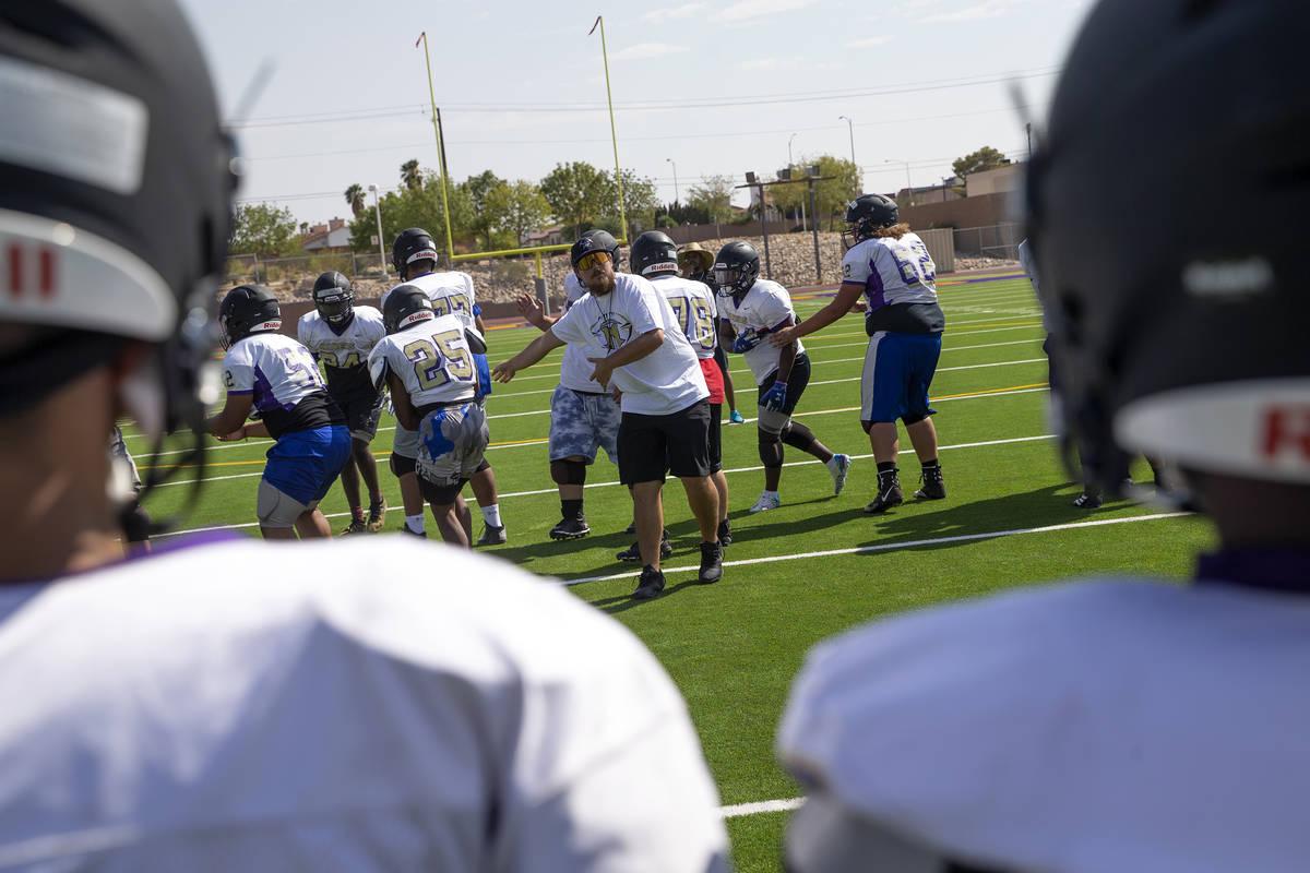 El entrenador Joshua Bennett, al centro, dirige la práctica del equipo de fútbol americano en ...