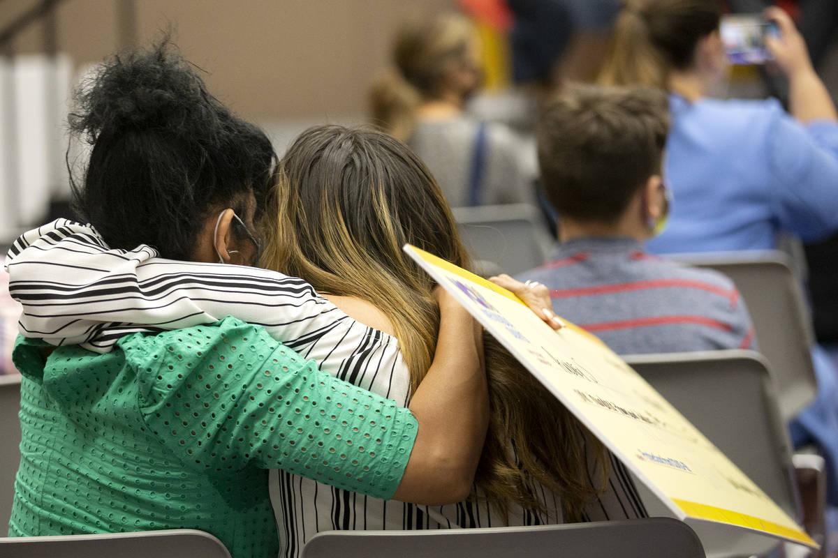 Audrey S. abraza a un ser querido mientras sostiene su cheque de 100 mil dólares durante el an ...