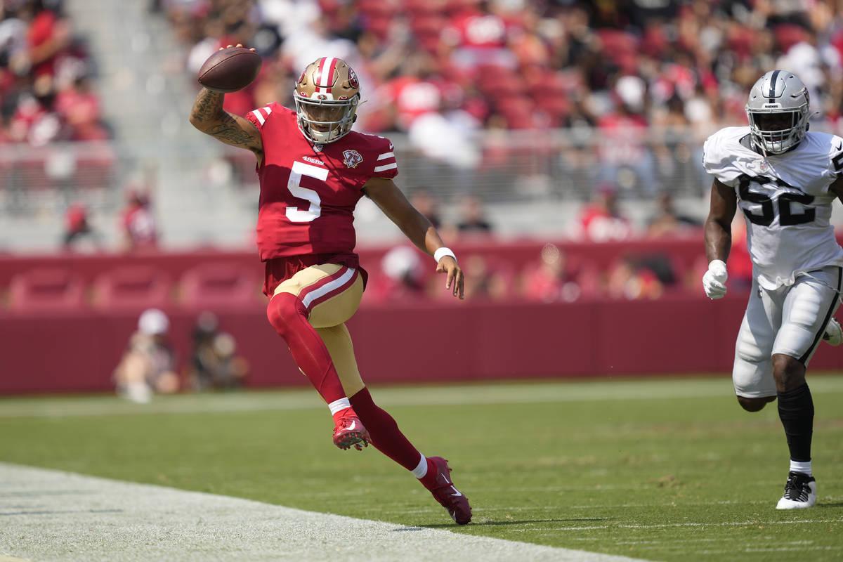 El quarterback de los San Francisco 49ers, Trey Lance (5), corre fuera de los límites contra l ...