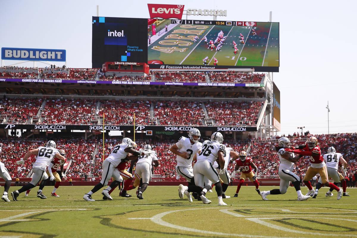 El quarterback de los Raiders de Las Vegas, Nathan Peterman (3), entrega el balón al running b ...