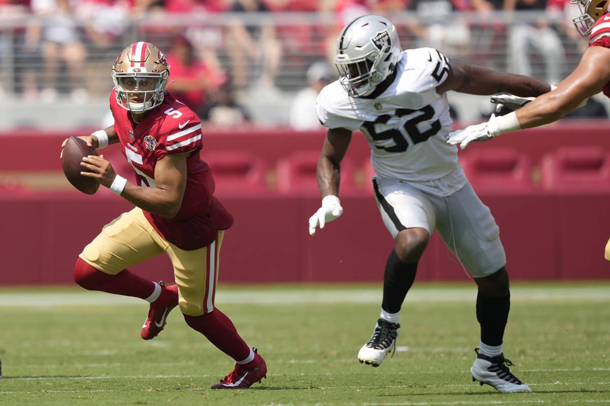 El quarterback de los 49ers de San Francisco, Trey Lance (5), se escapa del defensive end de lo ...