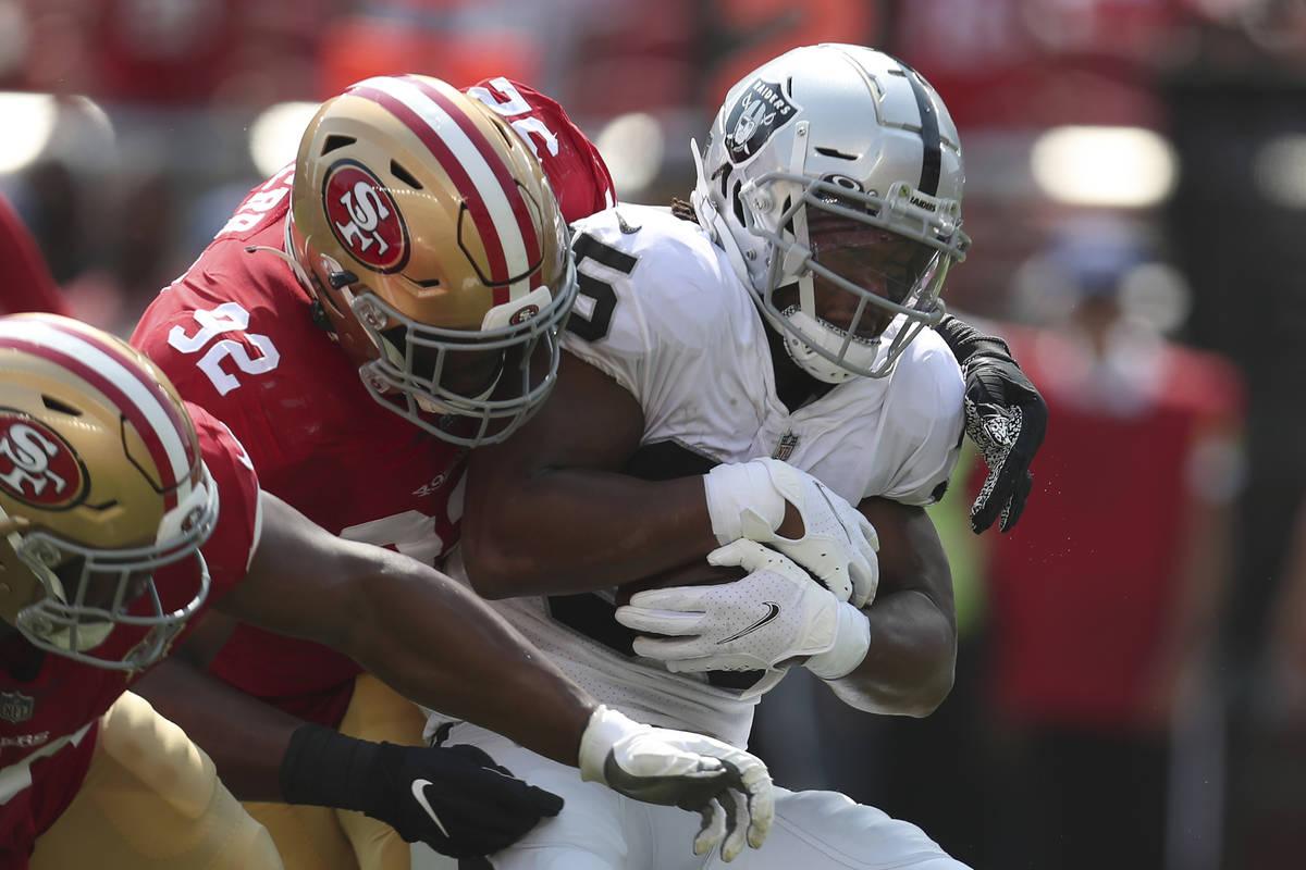 El defensive end de los San Francisco 49ers, Zach Kerr (92), tacklea al running back de los Las ...