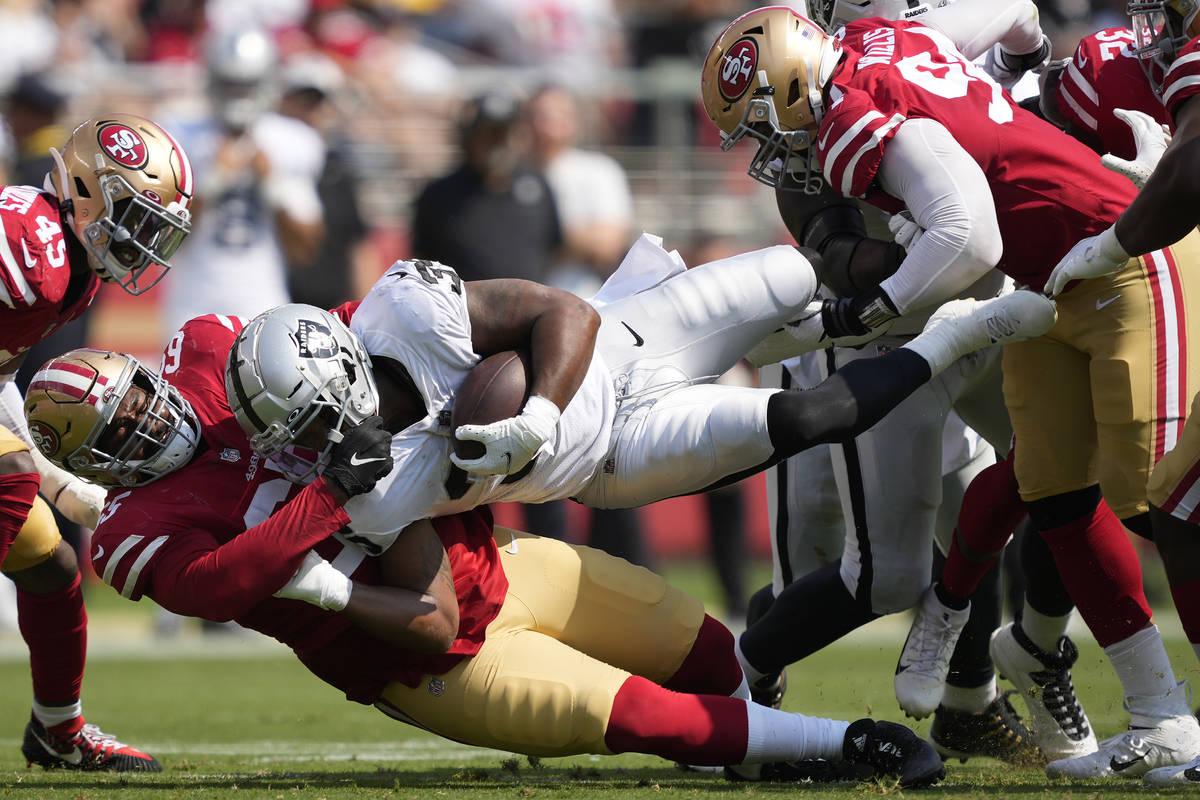 B.J. Emmons, de los Raiders de Las Vegas, en medio, es tackleado por los defensive linemen de l ...