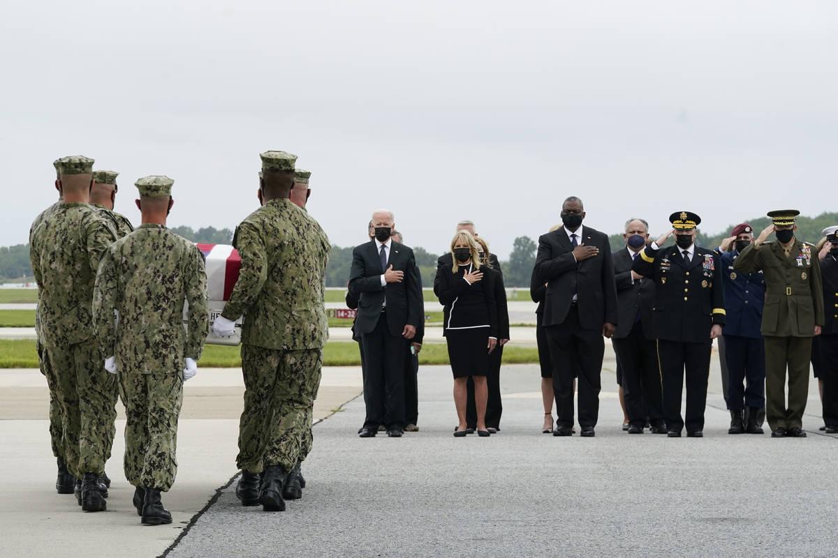 El presidente Joe Biden observa cómo un equipo de transporte de la Marina traslada una caja qu ...