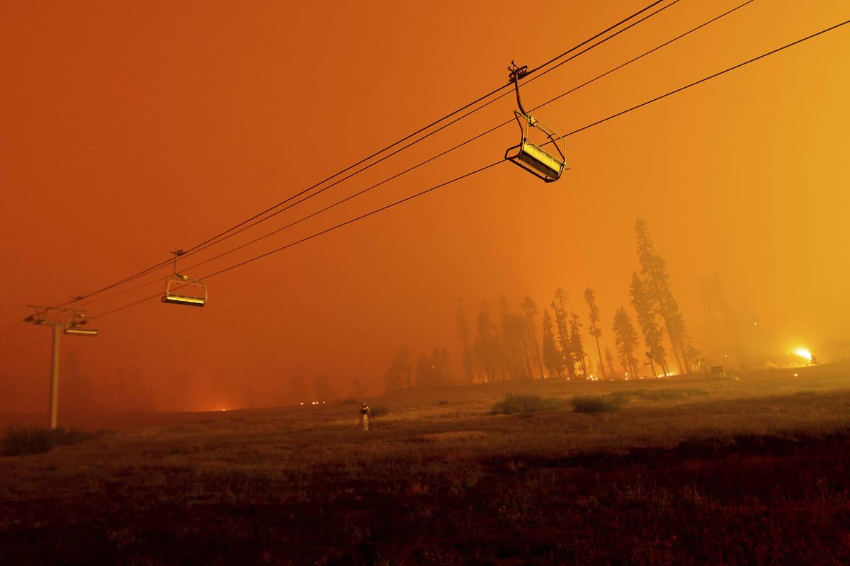 """Visto en una larga exposición de cámara, el """"Caldor Fire"""" arde mientras telesillas cuelgan en ..."""