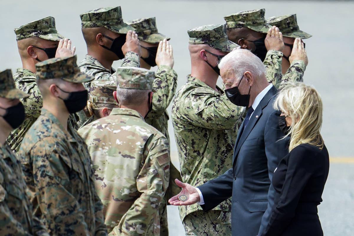 El presidente Joe Biden sostiene una moneda de desafío presidencial mientras habla con el Coro ...