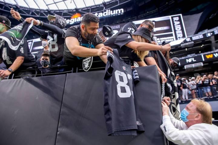 El propietario de los Raiders, Mark Davis, firma autógrafos para los fans antes del partido de ...
