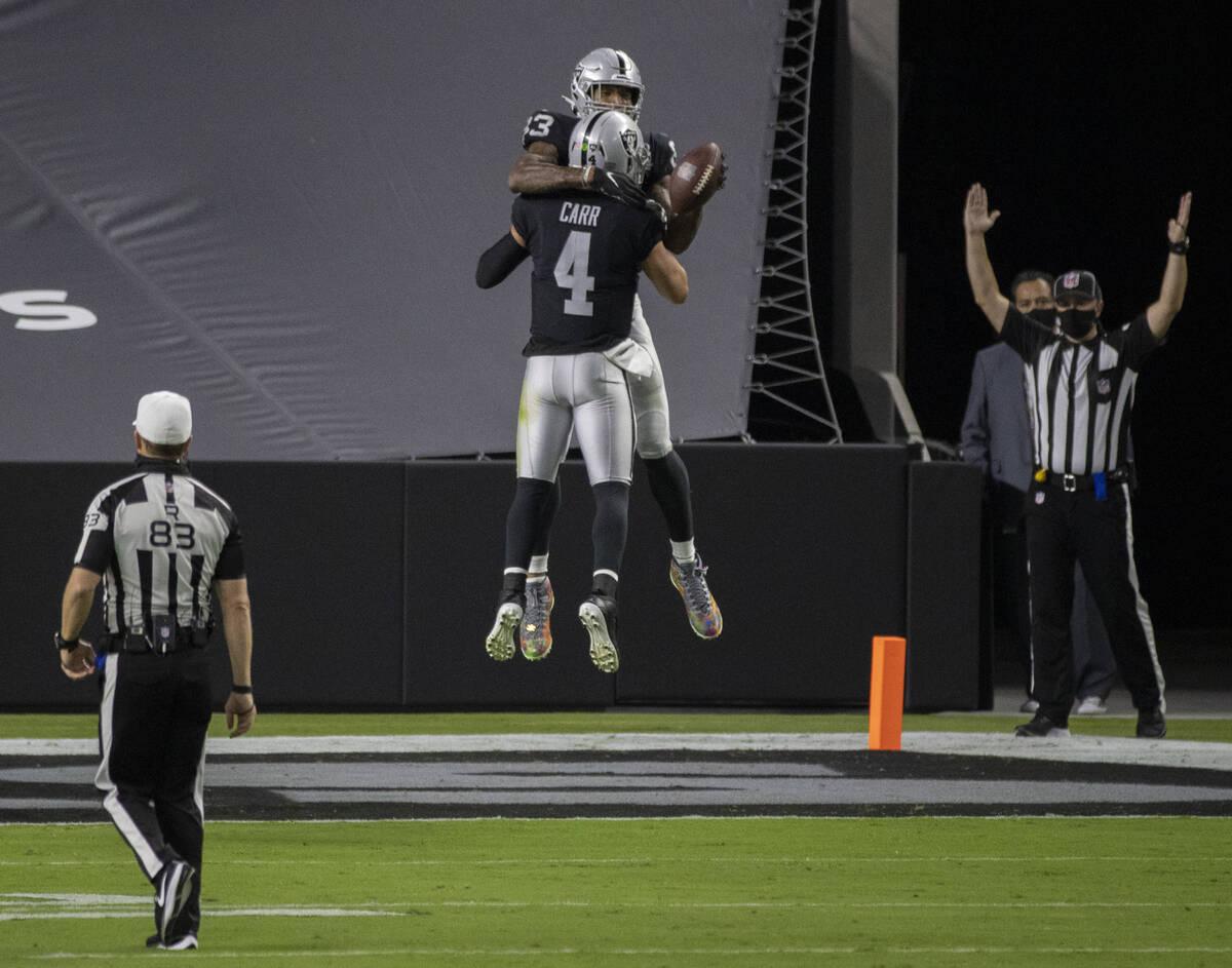 El quarterback de los Raiders de Las Vegas, Derek Carr (4), celebra con el tight end de los Rai ...
