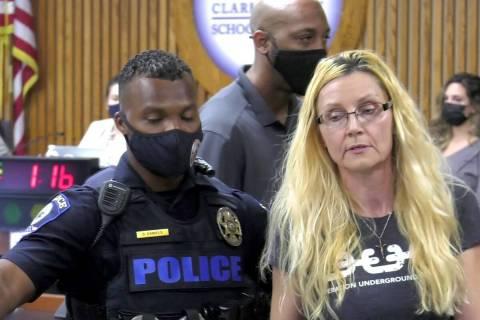 Personal de seguridad escolta a una mujer fuera de la reunión del jueves del Consejo Escolar d ...