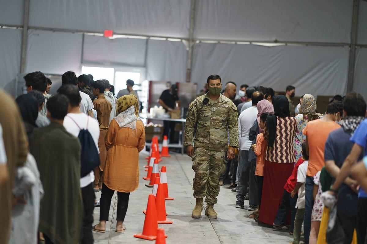Refugiados afganos hacen fila para recibir comida en un comedor en la Aldea Doña Ana de Fort B ...