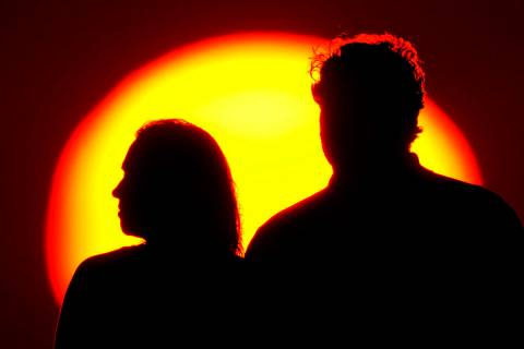 Una pareja observa la puesta de sol desde un parque el sábado 10 de julio de 2021 en Kansas Ci ...