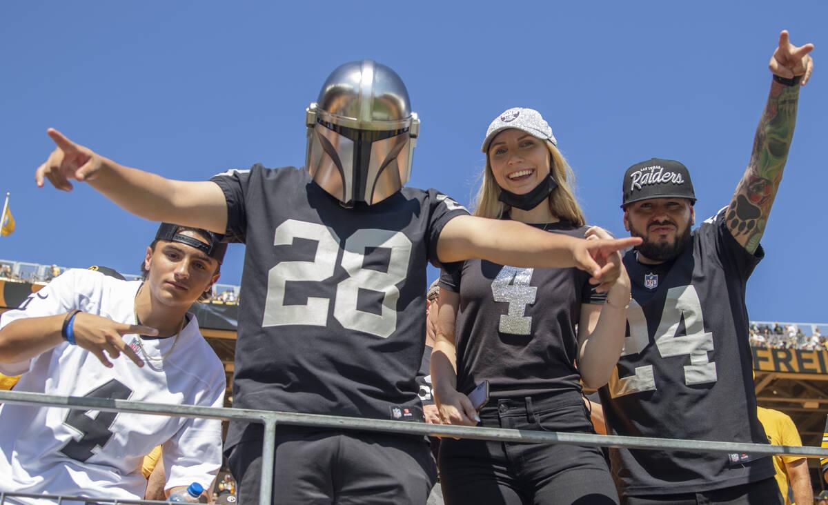 Fans de los Raiders animan al equipo durante el calentamiento antes de un partido de fútbol am ...