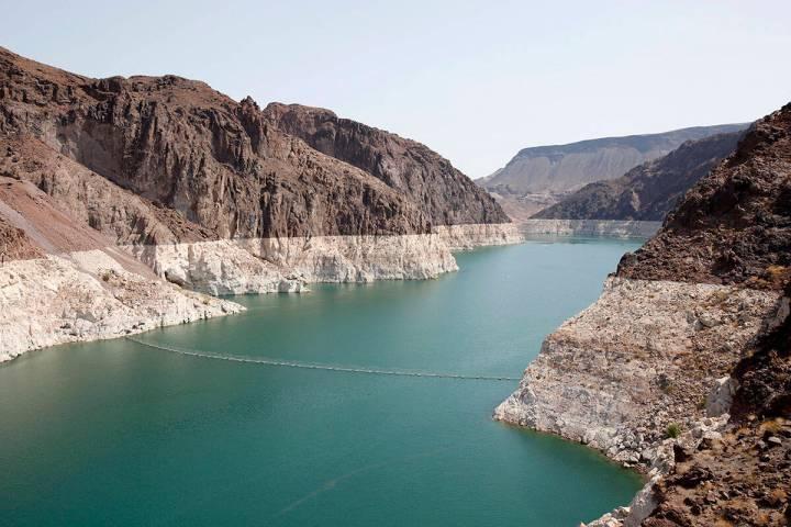 Un anillo de minerales claros muestra la línea de agua alta cerca de la presa Hoover en el Lag ...