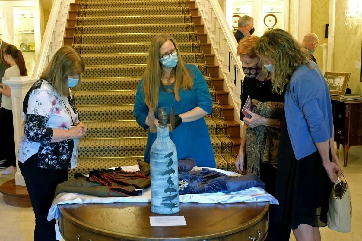 Los visitantes miran las telas que se exhiben el lunes como parte de una exposición en la mans ...