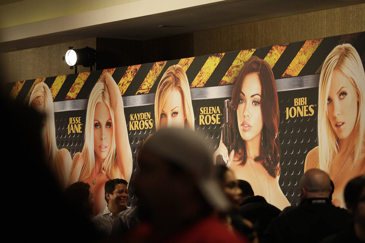 Una multitud pasa por delante de una pancarta que anuncia a las estrellas del cine para adultos ...