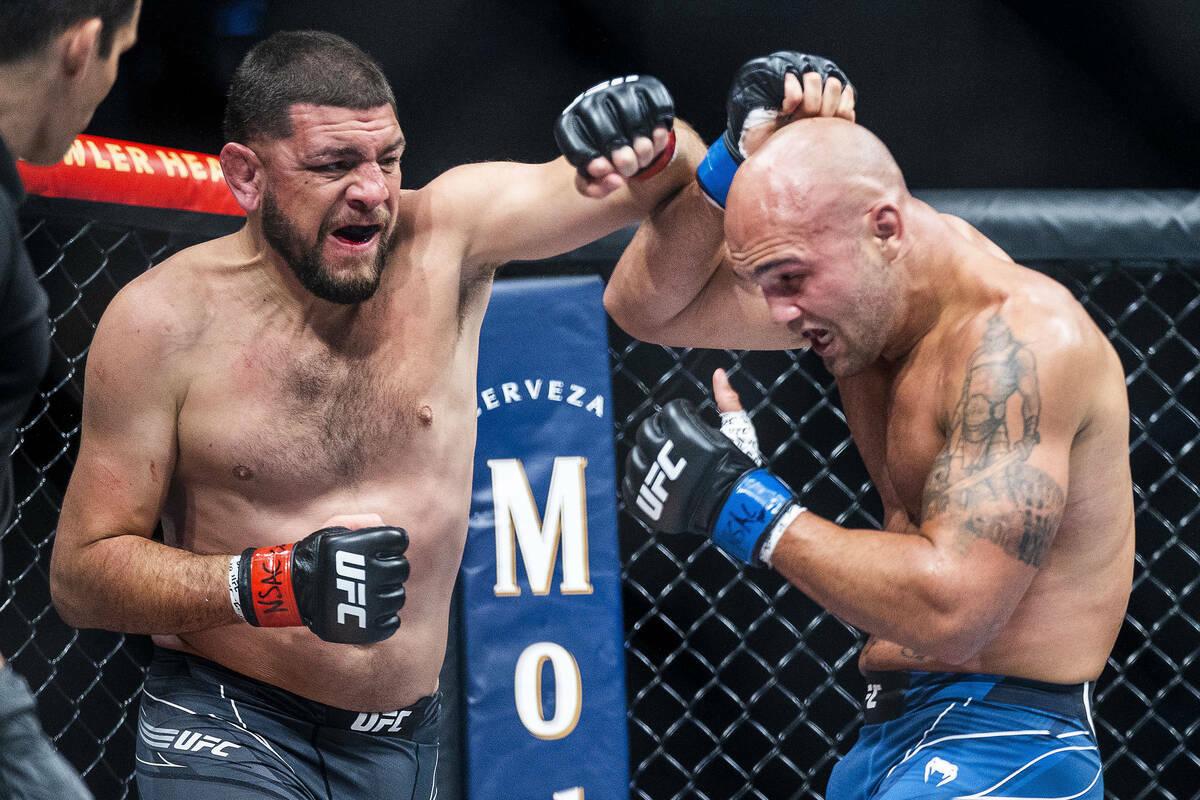 Nick Díaz, a la izquierda, pelea con Robbie Lawler en el tercer asalto durante su pelea de pes ...