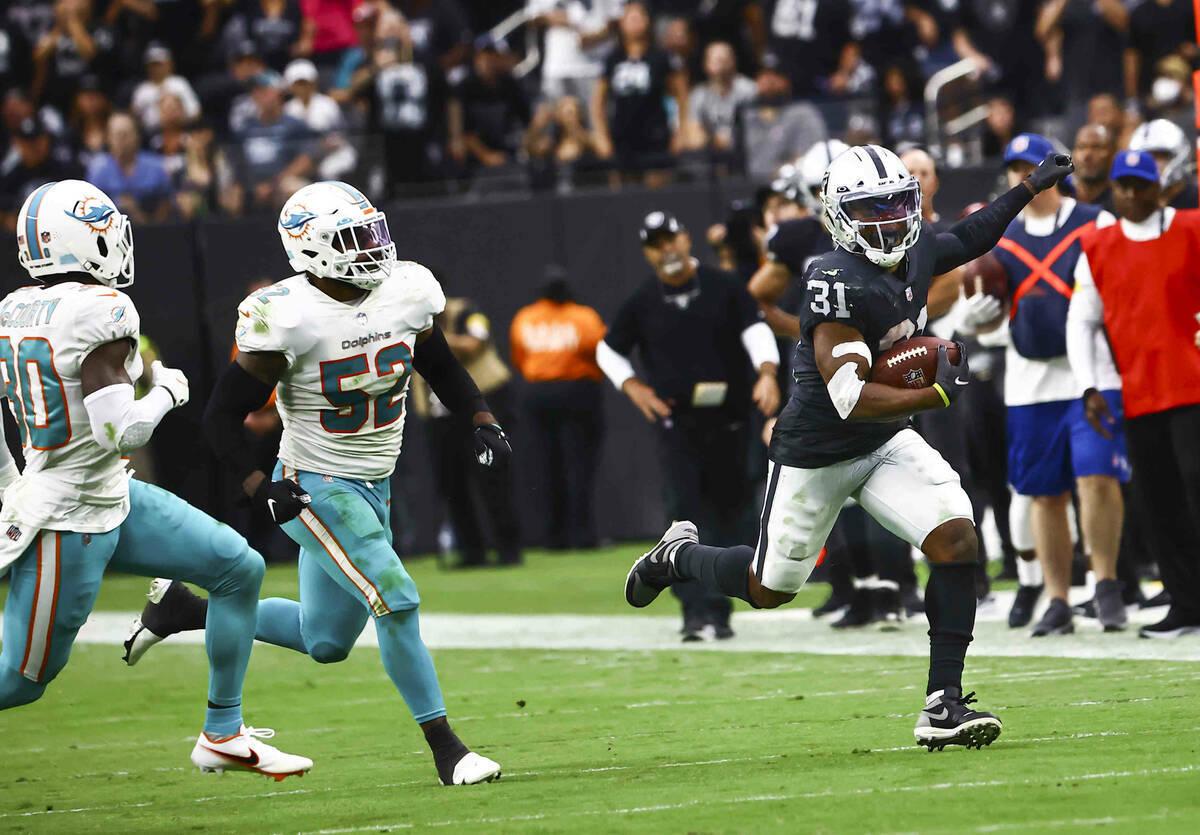 El corredor de los Raiders, Peyton Barber (31), corre con el balón ante su adversario de los M ...