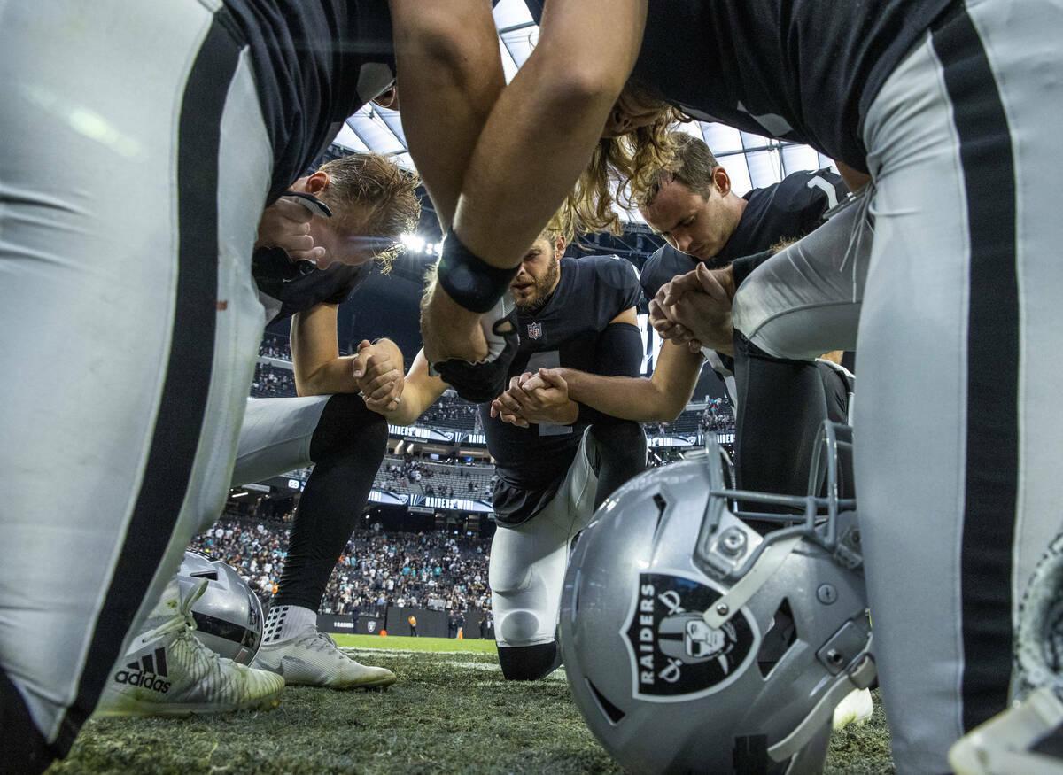 Los jugadores de los Raiders rezan juntos en el campo después de derrotar a los Miami Dolphins ...