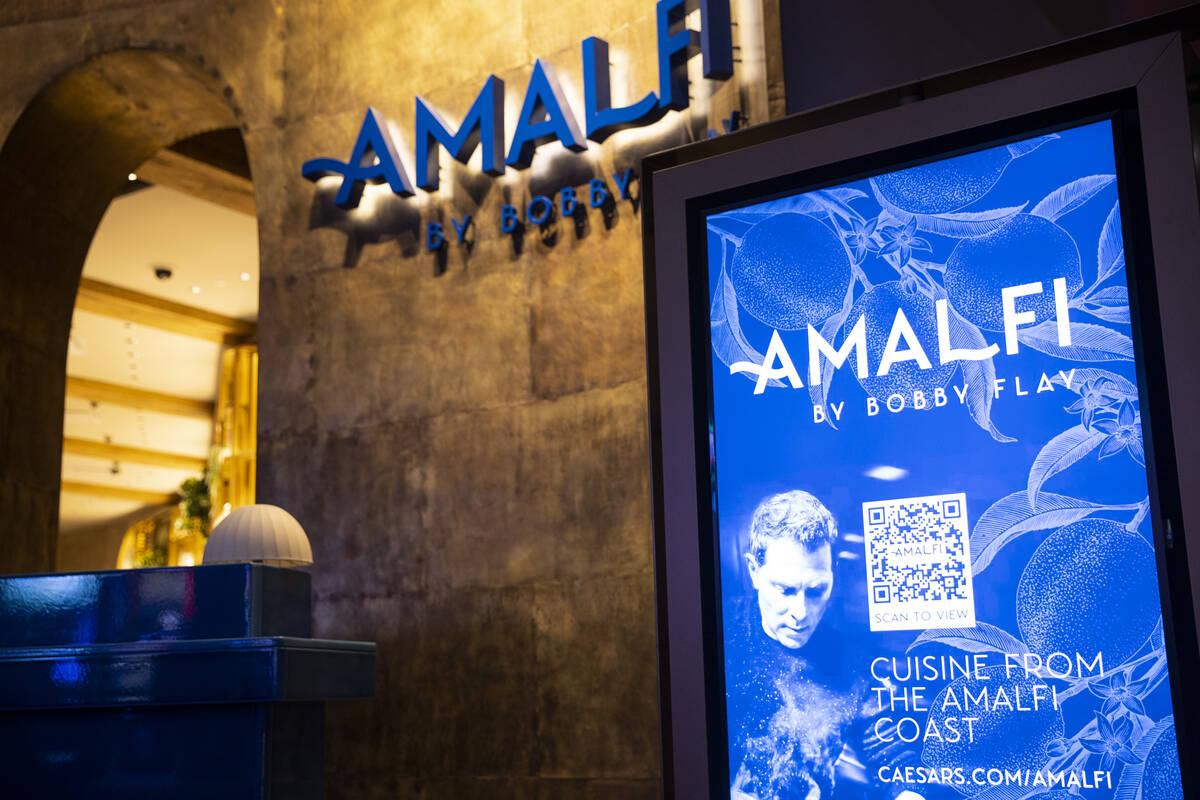 Un letrero muestra la información de un código QR para acceder al menú del restaurante Amalf ...