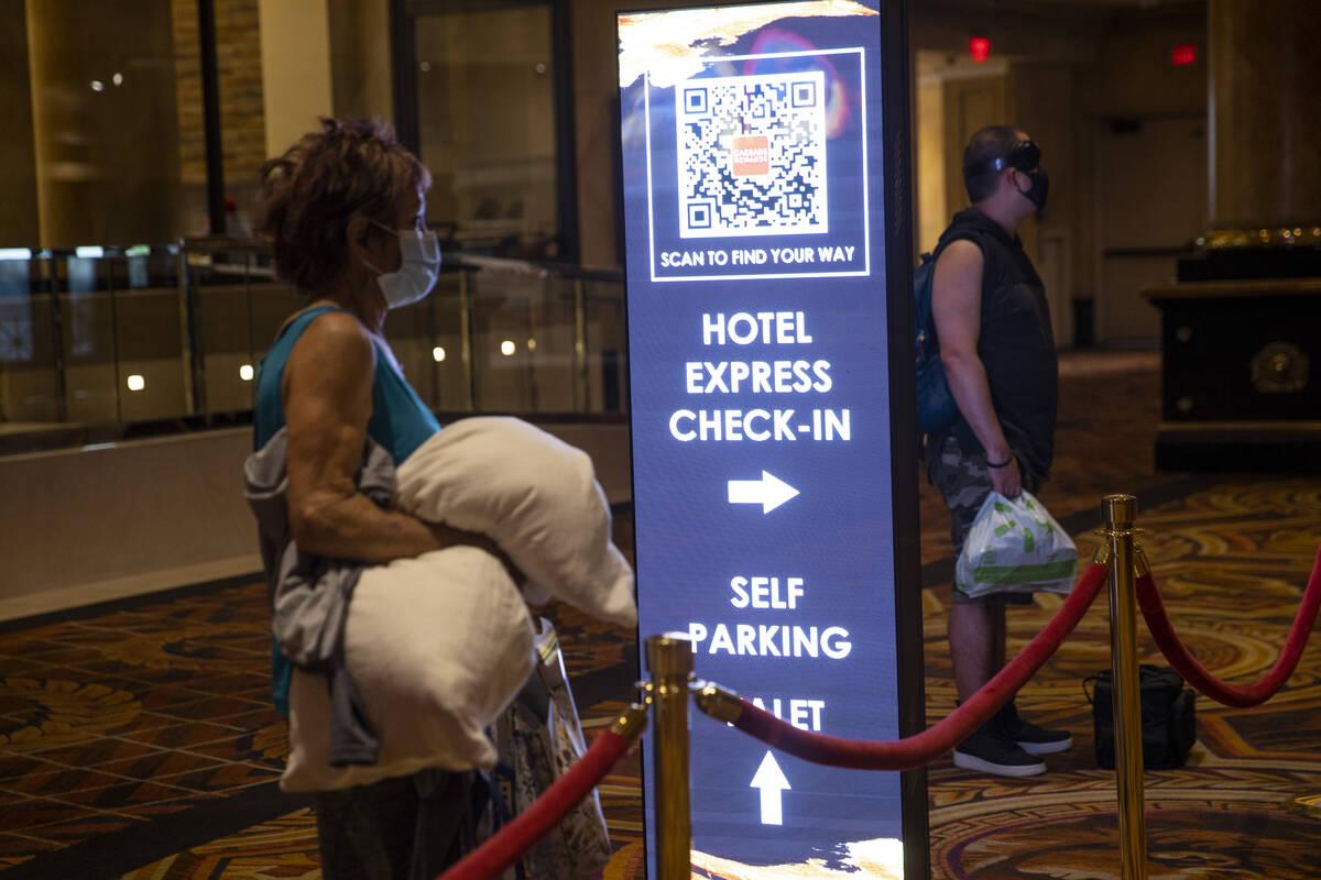 Un letrero dirige a los huéspedes a las nuevas máquinas que permiten un auto registro en el h ...