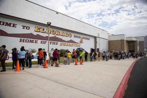 Gente hace fila durante una clínica de vacunación COVID-19 emergente en Eldorado High School ...