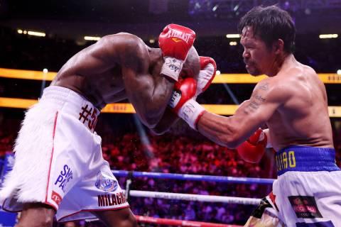 Yordenis Ugas, a la izquierda, recibe un golpe de Manny Pacquiao en el sexto asalto del combate ...