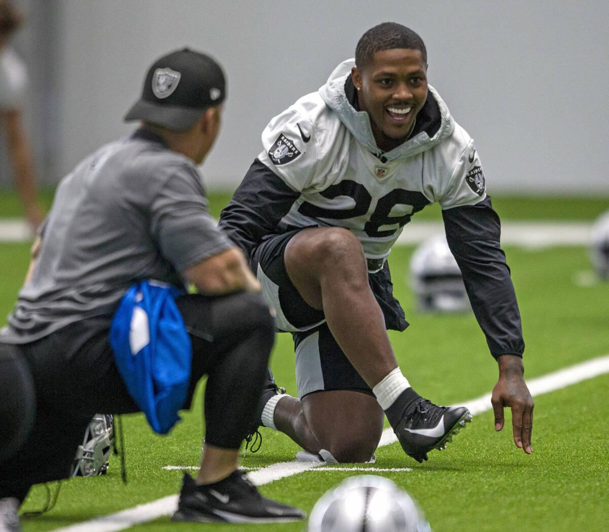 El running back de los Raiders Josh Jacobs (28) se ríe mientras estira durante una sesión de ...