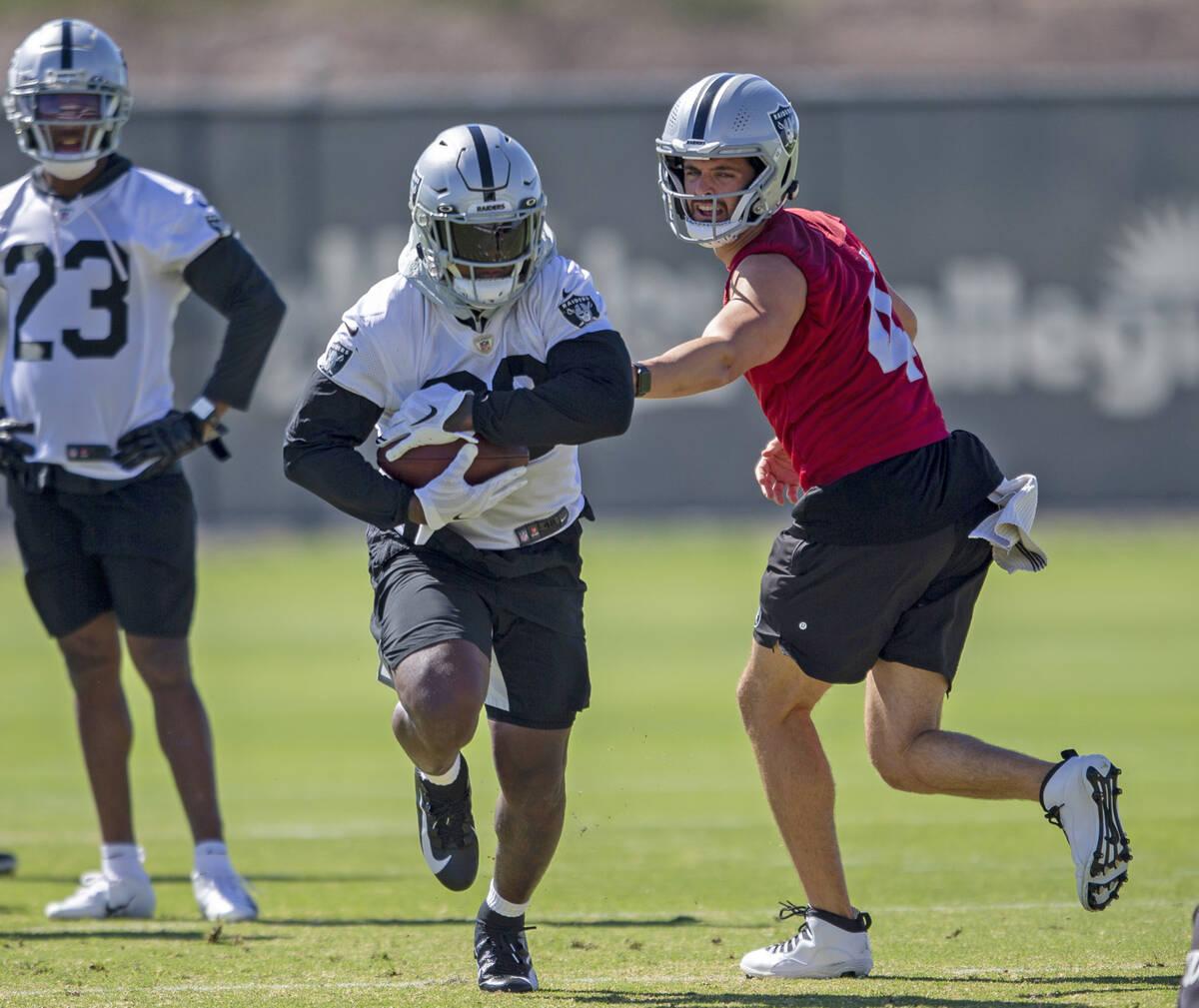 El quarterback de los Raiders, Derek Carr (4), entrega el balón al running back de los Raiders ...