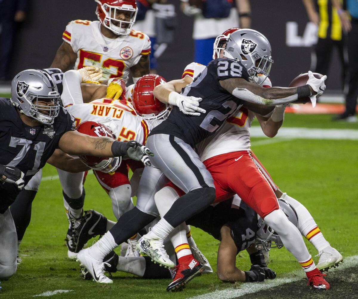El running back de los Raiders de Las Vegas, Josh Jacobs (28), alcanza el balón a través de l ...