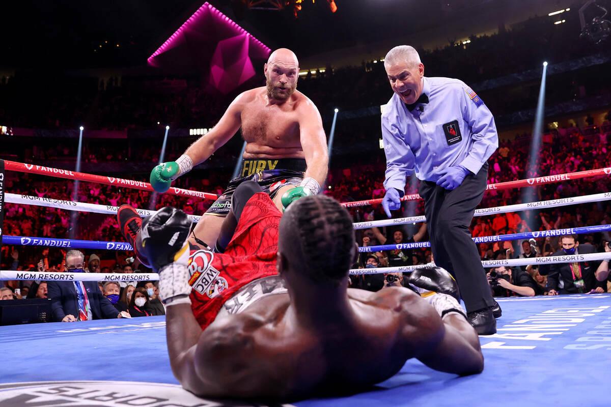 Tyson Fury, izquierda, derriba a Deontay Wilder en el tercer asalto de una pelea por el Campeon ...