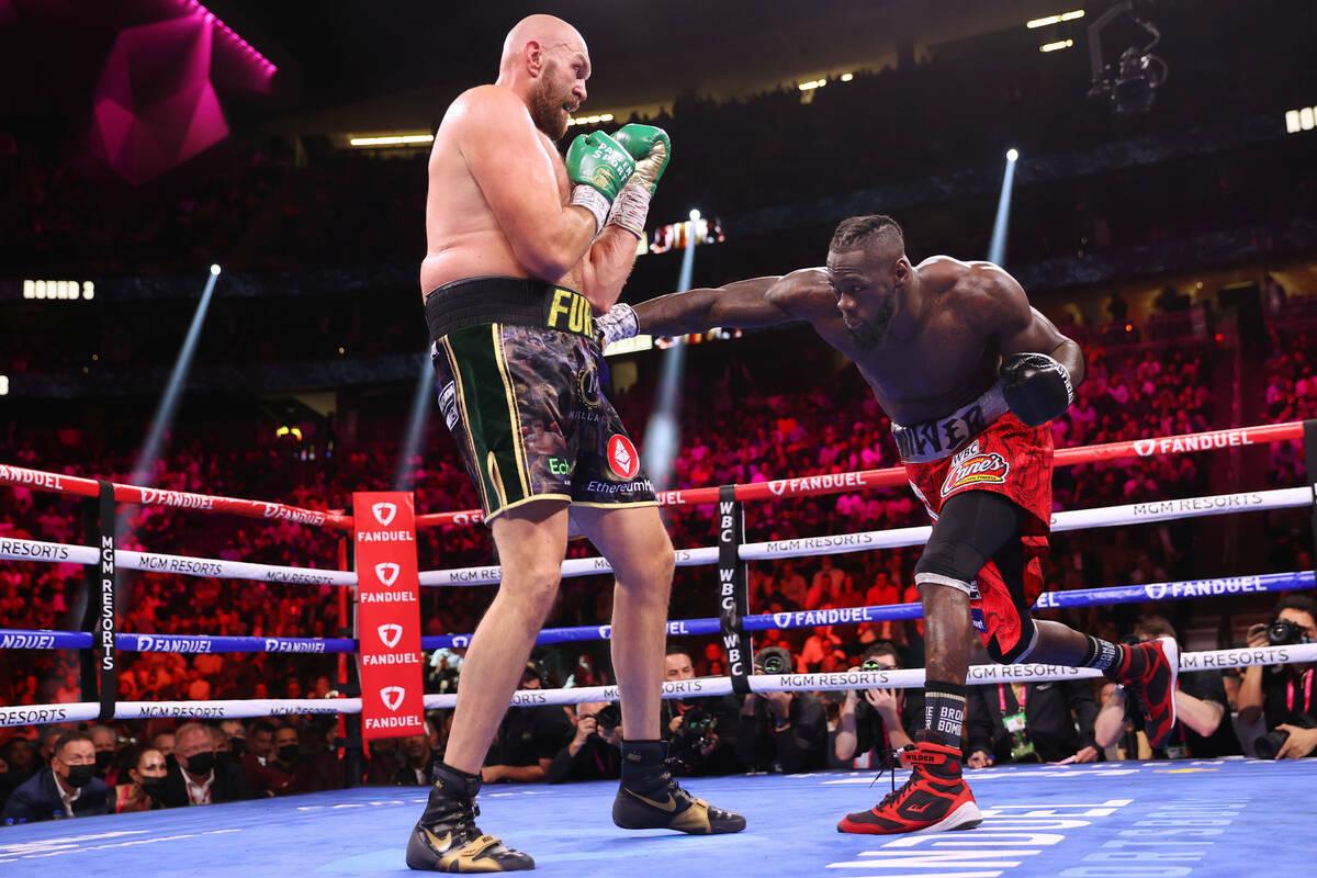 Deontay Wilder, a la derecha, lanza un puñetazo contra Tyson Fury en el tercer asalto de una p ...