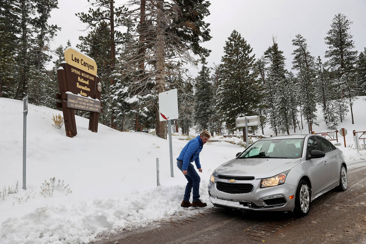 Garret Paus of Las Vegas puts tire chains on his car in Lee Canyon on Mount Charleston northwes ...