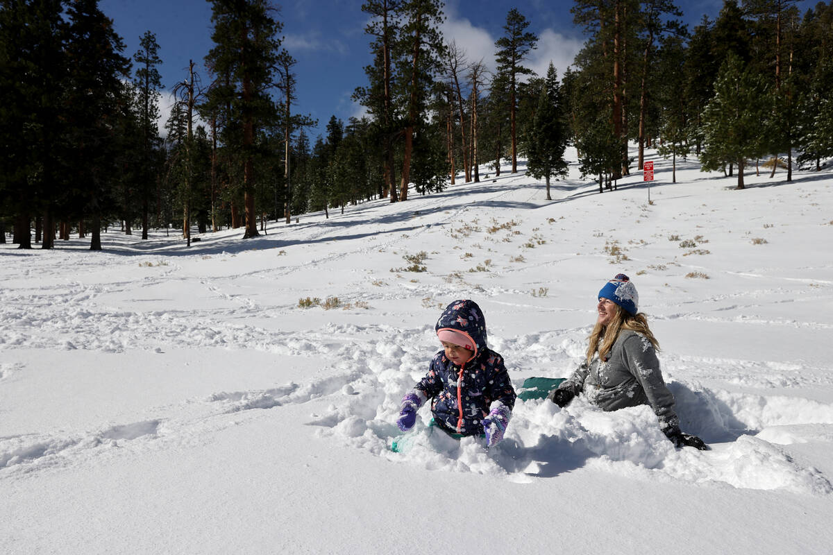Ava Parker, 2, and her mom Amy of Las Vegas play in freshly fallen snow in Upper Lee Meadows on ...