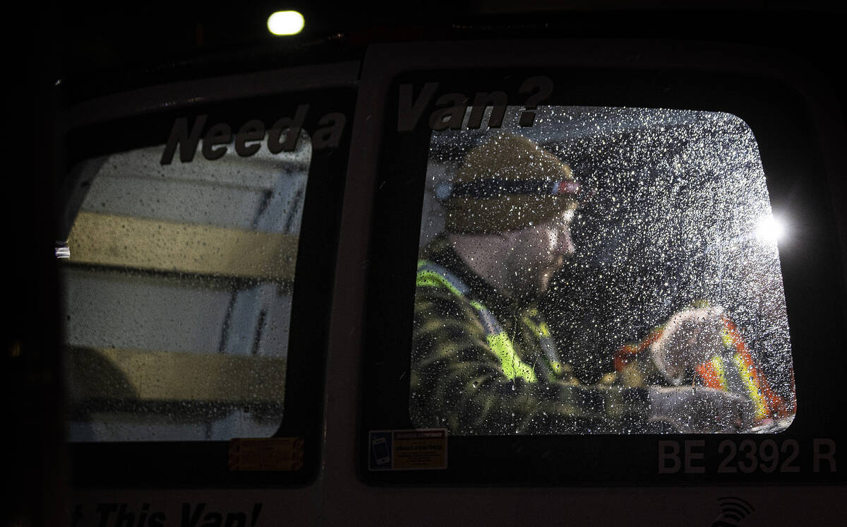Workers prep gear in their van before starting to attempt to restore power during an outage at ...
