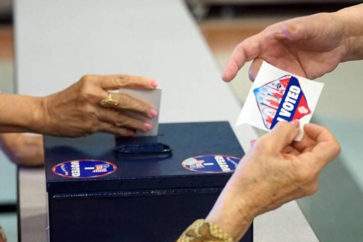 Un trabajador electoral entrega a un votante una calcomanía que muestra que votó mientras otr ...