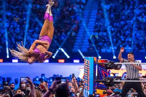 Charlotte Flair vuela desde las cuerdas superiores sobre Nikki A.S.H. y Rhea Ripley abajo en el ...