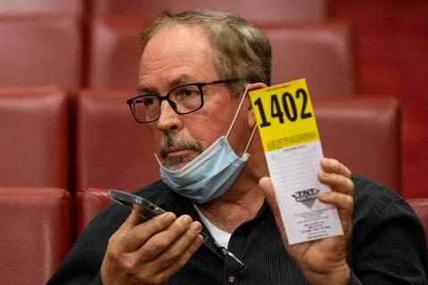 Dave Vale, gerente de distrito de Cash America, levanta su número para una oferta durante la 2 ...